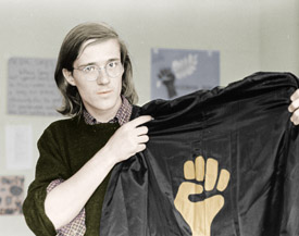 Student holding academic gown adorned with Black Power symbol, 1970