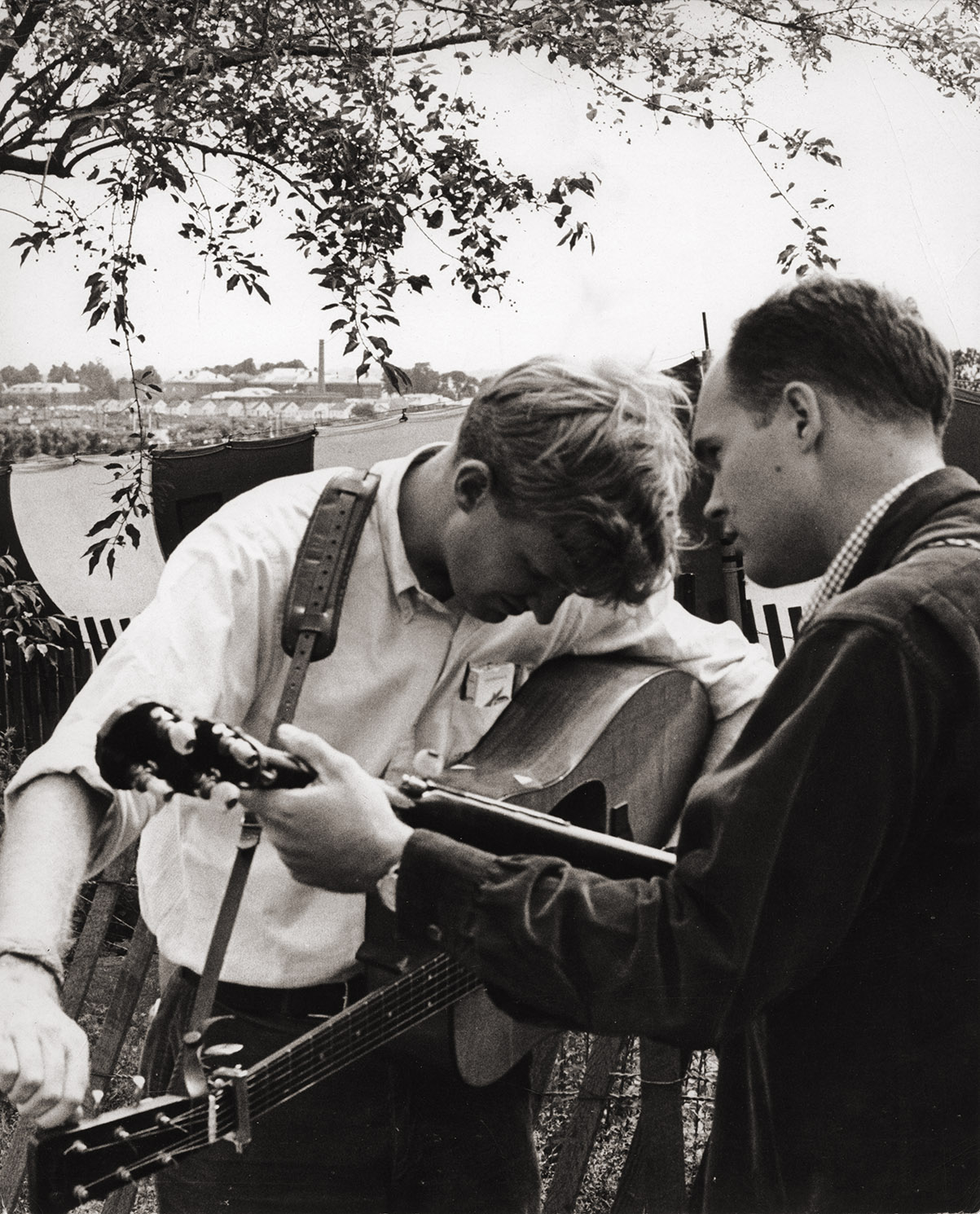 An image of: Jim Rooney, tuning his guitar, and Bill Keith at the Newport Folk Festival, 1965