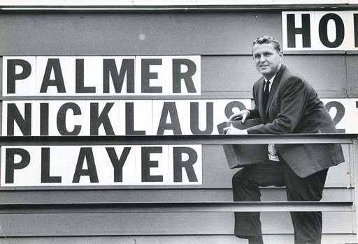 Mark H. McCormack in front of leaderboard, ca. early 1960s
