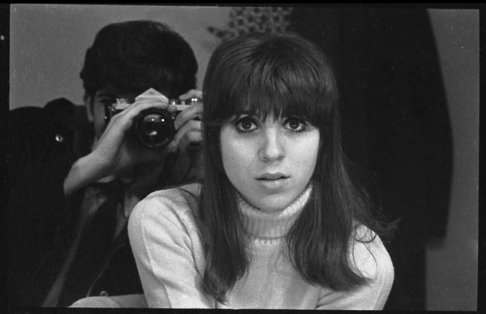 Depiction of Peter Simon in mirror photographing Jennie Blackton at the Bitter End Cafe, 1968