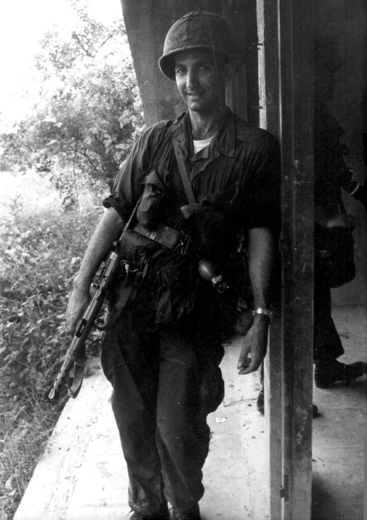 Daniel Ellsberg is smiling leaning on a post on his left shoulder in army fatigues with an M16 machine gun in his right hand pointed at the ground
