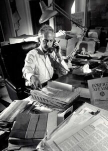 Daniel Ellsberg is seated at his desk with a telephone in his left hand while reaching for a paper on his desk.