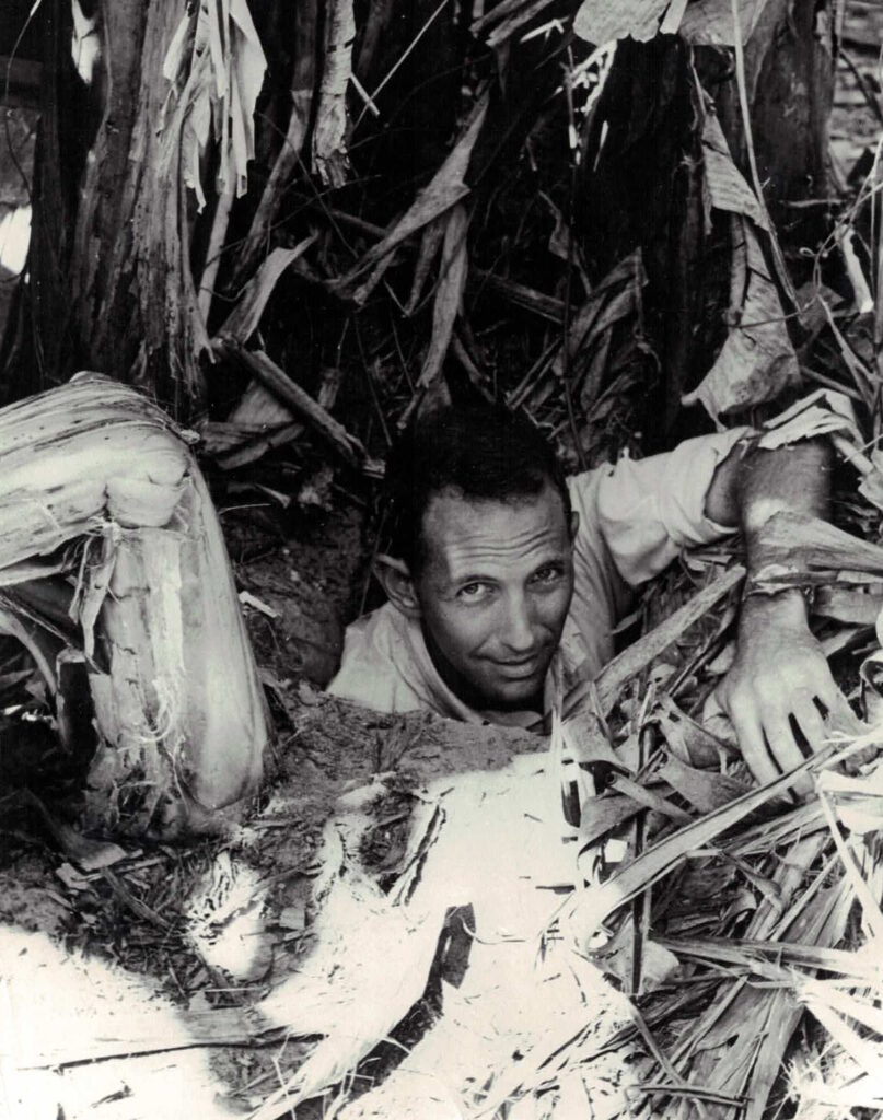 Dan Ellsberg emerging from a hole in the ground with his left hand on the ground looking at the camera