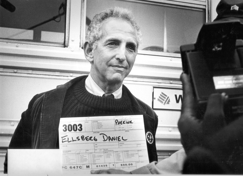 Daniel Ellsberg holding an arrest card being photographed by police in front of a school bus